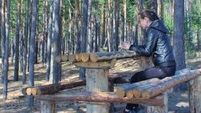 Jovem mulher que senta-se no banco de madeira usando o telefone no outono da floresta do parque vídeos de arquivo