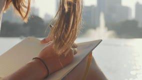 Jovem mulher que senta-se no banco no parque e que escreve no diário, close-up video estoque