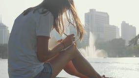 Jovem mulher que senta-se no banco no parque e que escreve no diário, close-up filme