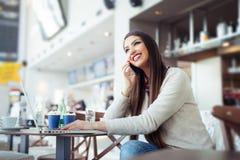 Jovem mulher que senta-se no bar com portátil e que usa o telefone celular Fotos de Stock Royalty Free