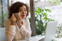 Jovem mulher que senta-se no café com portátil e um copo do chá em suas mãos Foto de Stock Royalty Free