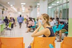 Jovem mulher que senta-se no hospital que espera a nomeação de um doutor Pacientes nos doutores sala de espera fotos de stock royalty free