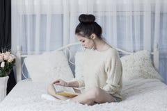 Jovem mulher que senta-se no mau em casa e que lê um livro Fotos de Stock Royalty Free