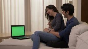 Jovem mulher que senta-se no regaço de seu noivo em um sofá branco em casa que olha um filme no portátil video estoque