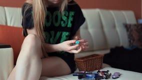 A jovem mulher que senta-se no sofá abre e desenrola o batom video estoque