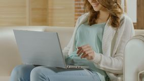 Jovem mulher que senta-se no sofá e que conversa com o noivo no portátil, abrandamento vídeos de arquivo