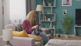 Jovem mulher que senta-se no sofá e no curso de confecção de malhas de observação no smartphone filme