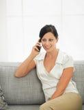 Jovem mulher que senta-se no sofá e no móbil de fala imagem de stock