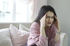 Jovem mulher que senta-se no sofá em casa com uma dor de cabeça imagens de stock