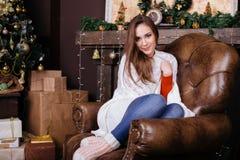 Jovem mulher que senta-se no sofá, sozinho, na frente da árvore de Natal na sala de visitas Fotos de Stock Royalty Free