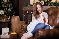 Jovem mulher que senta-se no sofá, sozinho, na frente da árvore de Natal na sala de visitas Fotografia de Stock