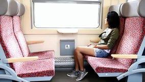 Jovem mulher que senta-se no trem video estoque