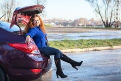 Jovem mulher que senta-se no tronco de carro Fotos de Stock