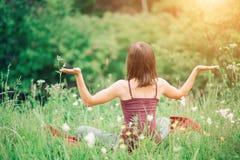 A jovem mulher que senta-se para trás com suas mãos abre na natureza no verão em um dia ensolarado A saúde, ioga, harmonia, relax imagem de stock royalty free