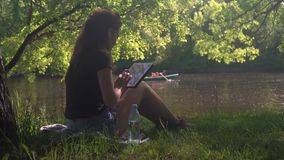 Jovem mulher que senta-se pelo rio no parque e no uso filme