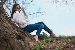 Mulher que senta-se sob uma árvore Foto de Stock Royalty Free