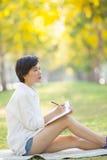 A jovem mulher que sentam-se no parque da grama verde com lápis e a nota vaiam Fotografia de Stock