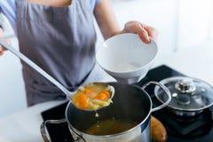 Jovem mulher que serve a sopa vegetal na cozinha Imagem de Stock Royalty Free