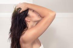 Jovem mulher que shampooing seu cabelo marrom longo imagens de stock