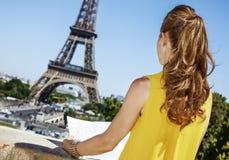 Jovem mulher que sightseeing na frente da torre Eiffel em Paris fotografia de stock