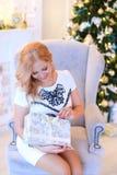 Jovem mulher que sittling na cadeira com atual, árvore do braço de Christams no fundo Fotos de Stock