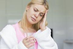 Jovem mulher que sofre da dor de cabeça ao guardar o vidro da água Fotografia de Stock