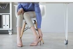 Jovem mulher que sofre da dor do pé no escritório fotografia de stock royalty free