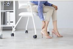 Jovem mulher que sofre da dor do pé no escritório fotos de stock royalty free