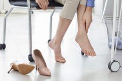 Jovem mulher que sofre da dor do pé no escritório fotos de stock