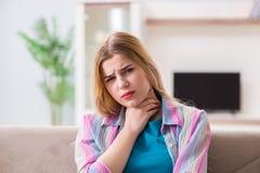 A jovem mulher que sofre da dor da garganta inflamada fotos de stock