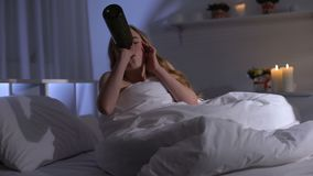 Jovem mulher que sofre a depressão principal, vinho bebendo na cama, apego de álcool video estoque
