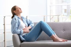 Jovem mulher que sofre dos grampos menstruais fotos de stock royalty free
