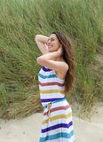 Jovem mulher que sorri com mão no cabelo Imagens de Stock Royalty Free