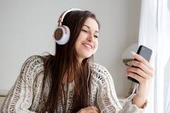 Jovem mulher que sorri com telefone celular e que escuta a música com fones de ouvido foto de stock royalty free