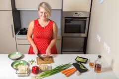 Jovem mulher que sorri e que corta o aspargo na cozinha Foto de Stock