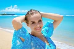 Jovem mulher que sorri na câmera na frente do mar Imagem de Stock Royalty Free