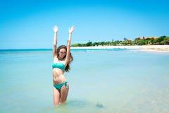 Jovem mulher que sorri na câmera na frente do mar Fotografia de Stock