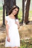 Jovem mulher que sorri no vestido branco nas madeiras Foto de Stock Royalty Free