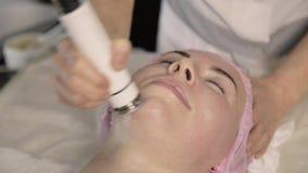 Jovem mulher que submete-se ao tratamento da pele Melhorando o olhar sem cirurgia RF que levanta em uma cara video estoque