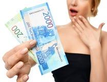 Jovem mulher que sustenta o dinheiro do dinheiro dois mil e cem vencedores disponivéis das notas dos rublos de russo surpreendido Fotografia de Stock