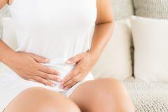 Jovem mulher que tem a dor de estômago dolorosa que senta-se no sofá em casa fotografia de stock royalty free