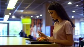 Jovem mulher que tem o almoço na cantina, comendo a tabela de assento do café da salada vegetal imagens de stock