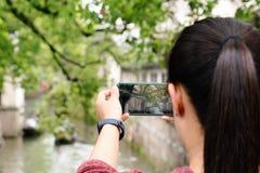 Jovem mulher que tem o divertimento na cidade local do canal em China com a c?mera no smartphone que faz imagens imagem de stock