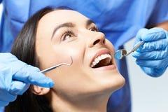 Jovem mulher que tem o exame ascendente e dental da verificação no dentista fotografia de stock royalty free