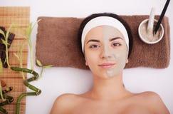 Jovem mulher que tem o tratamento da máscara da pele da argila em sua cara Fotografia de Stock Royalty Free