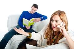 Jovem mulher que tem um argumento em seu telefone enquanto seu noivo lê Fotos de Stock