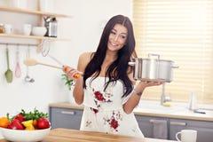 Jovem mulher que tenta cozinhar algo na cozinha fotos de stock