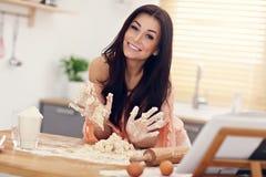 Jovem mulher que tenta fazer o pierogi na cozinha fotos de stock