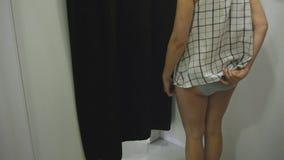 Jovem mulher que tenta na roupa Incline a ideia da vista fêmea caucasiano atrativa na tentativa de giro do espelho na blusa filme