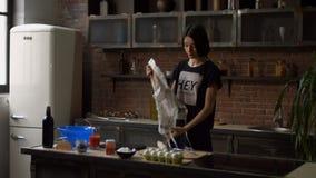 Jovem mulher que tenta no avental que prepara-se para cozinhar video estoque